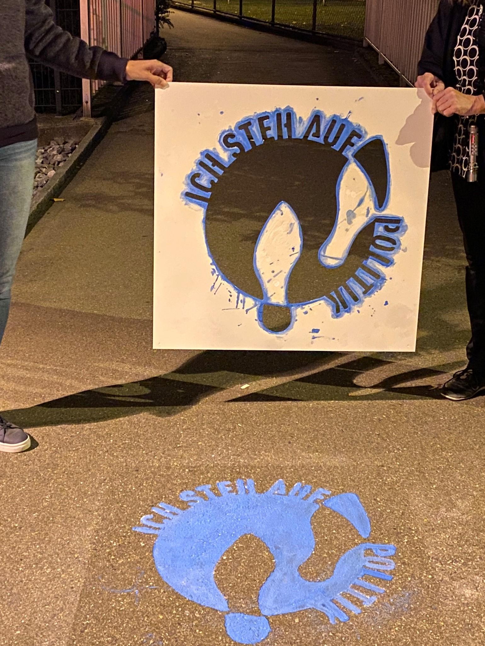 """Auf dem Boden ist das Logo """"Ich steh auf Politik"""" zu sehen. Darüber halten zwei Hände die Schablone."""