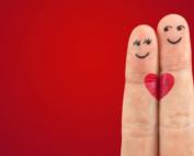 Zwei Finger mit je einem aufgemalten weiblichen und männlichen Gesicht sowie einem roten Herzen